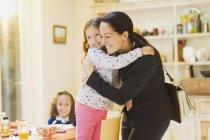 Madre trabajadora abrazando a su hija adiós en la mesa del desayuno - foto de stock
