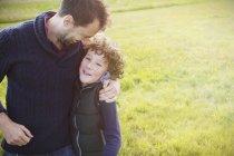 Padre che abbraccia il figlio sul campo — Foto stock