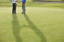 Imagen recortada de senior masculino estrecharme la mano en el campo de golf - foto de stock