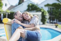Пара отдыха в шезлонге у бассейна — стоковое фото