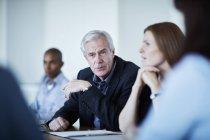 Homme d'affaires senior, écoute en réunion — Photo de stock