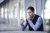 Successful adult businessman using cell phone outdoors — Stock Photo