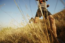 Man running through tall grass on sunny trail — Stockfoto