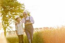 Avô agricultor falando com neto no campo de trigo rural ensolarado — Fotografia de Stock