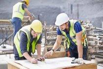 Строитель и инженер пересматривают чертежи на строительной площадке — стоковое фото
