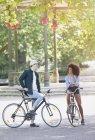 Amis sur les vélos parlant dans le parc urbain — Photo de stock