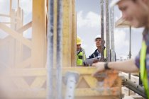 Foreman with digital tablet looking up at construction site — Stock Photo