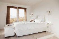 Cama interior acogedor dormitorio blanco - foto de stock