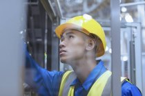 Worker in hard-hat examining machinery in factory — Stock Photo