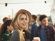 Portrait smiling young woman enjoying rooftop party — Stockfoto
