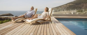 Пара пожилых людей отдыхает в шезлонгах у бассейна — стоковое фото
