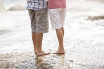 Couple de personnes âgées se tenant debout sur rock sur la plage — Photo de stock