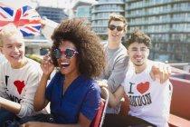 Portrait enthusiastic friends with British flag riding double-decker bus — Foto stock