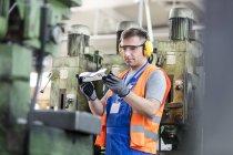 Trabajador en examinar parte de la fábrica de ropa protectora - foto de stock