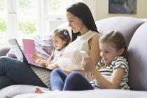 Madre e hijas con portátil, teléfono celular y tablet digital en el sofá - foto de stock