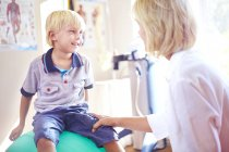 Physiothérapeute parler au garçon sur le ballon de fitness — Photo de stock