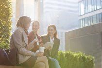 Smiling businesswomen with digital tablet drinking coffee outdoors — Stockfoto