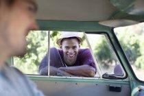 Smiling man leaning on camper van window — Stock Photo