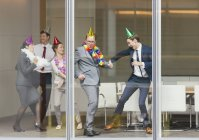 Playful business people in party hats dancing at conference room window — Stock Photo