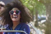 Mulher entusiástica com afro vestindo óculos em forma de coração — Fotografia de Stock
