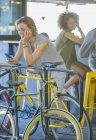 Donna sorridente appoggiata su ringhiera sms con cellulare sopra la bicicletta — Foto stock