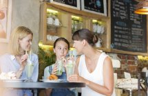 Zwei Frauen und Mädchen trinken Cocktails im café — Stockfoto