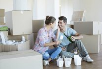 Couple drinking champagne and eating Chinese food on floor in new house — Stock Photo