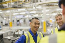 Workers in reflective clothing talking in factory — Stock Photo