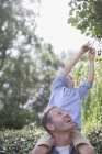 Father carrying son on shoulders outdoors — Stock Photo