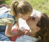 Close up mother and daughter kissing — Stock Photo