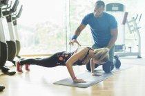 Persönlicher Trainer leiten Frau tun Liegestütze in Turnhalle — Stockfoto