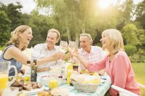 Couples toasting wine glasses at table in backyard — Stock Photo