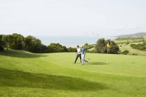 Men walking on golf course overlooking ocean — Stock Photo