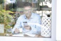 Homme utilisant smartphone tout en étant assis à la table de café — Photo de stock