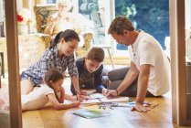 Family drawing and coloring on floor in living room — Stockfoto
