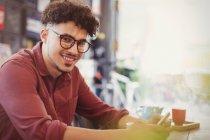 Porträt lächelnder Mann mit lockigem schwarzem Haar im Café — Stockfoto
