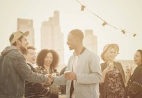 Young adult friends handshaking at rooftop party — Stockfoto