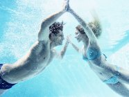 Young attractive couple touching hands underwater — Stock Photo