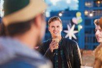 Jungen Erwachsenen Freunden sprechen und Trinken bei Nacht auf dem Dach-party — Stockfoto