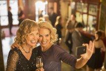 Donne ben vestite con champagne che fanno autoritratto con telefono nella hall del teatro — Foto stock