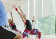 Fitness instructor leading aerobics class in high lunge — Stockfoto