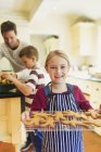 Girl holding cookie on platter, father and boy on background — Stock Photo