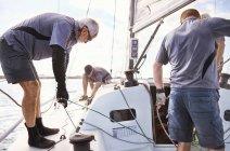Men sailing adjusting sailboat rigging — Stock Photo