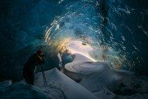 Фотограф в ледяной пещере — стоковое фото
