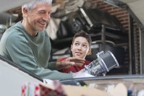 Smiling father and son fixing car engine in auto repair shop — Stock Photo