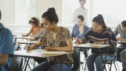 College students taking test at desks in classroom — Stock Photo