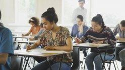 Étudiants du Collège prenant tester aux comptoirs dans la salle de classe — Photo de stock