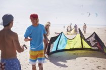 Men preparing kiteboarding kite on sunny beach — Stock Photo