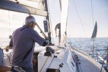 Человек, регулируя оборудование плавание на яхте — стоковое фото