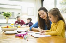 Mother and daughter doing homework at dining table — Stockfoto